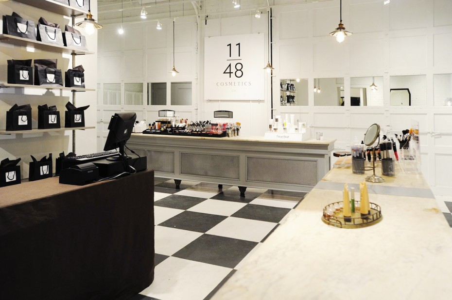 cosmetics store with black and white checked floor, vintage grey transaction counters with white marble tops, white garage doors with mirrored insets