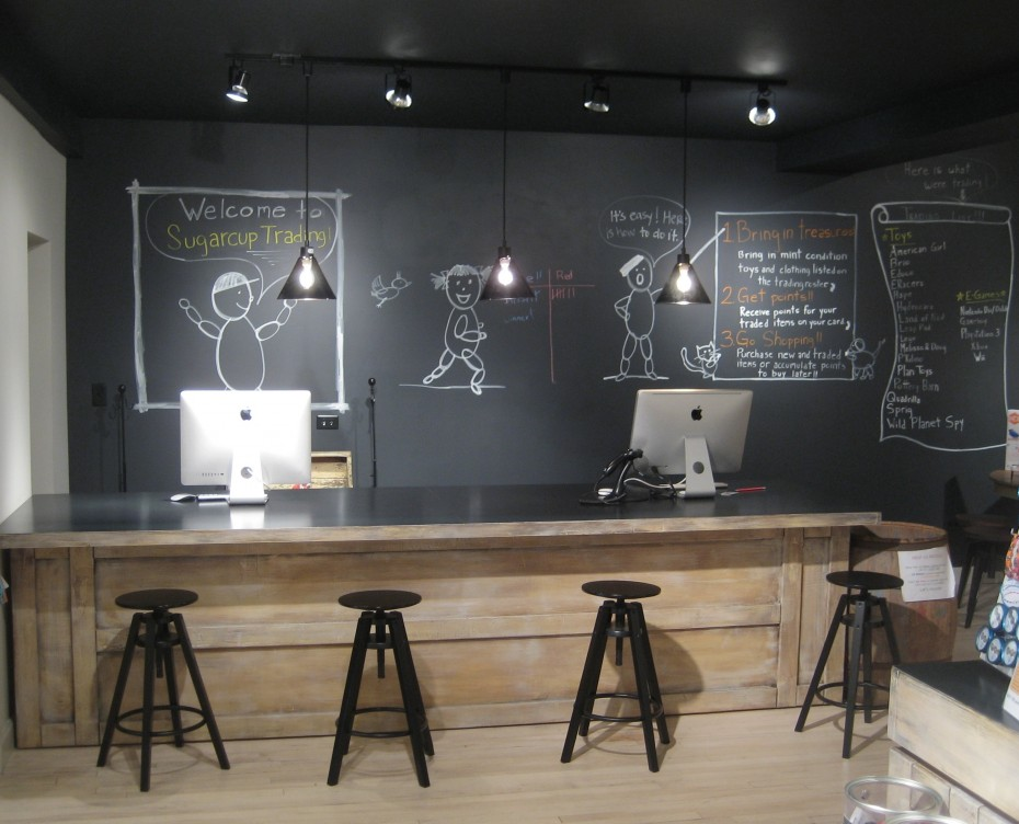 Children's retail store large chalkboard wall and custom transaction desk with stools