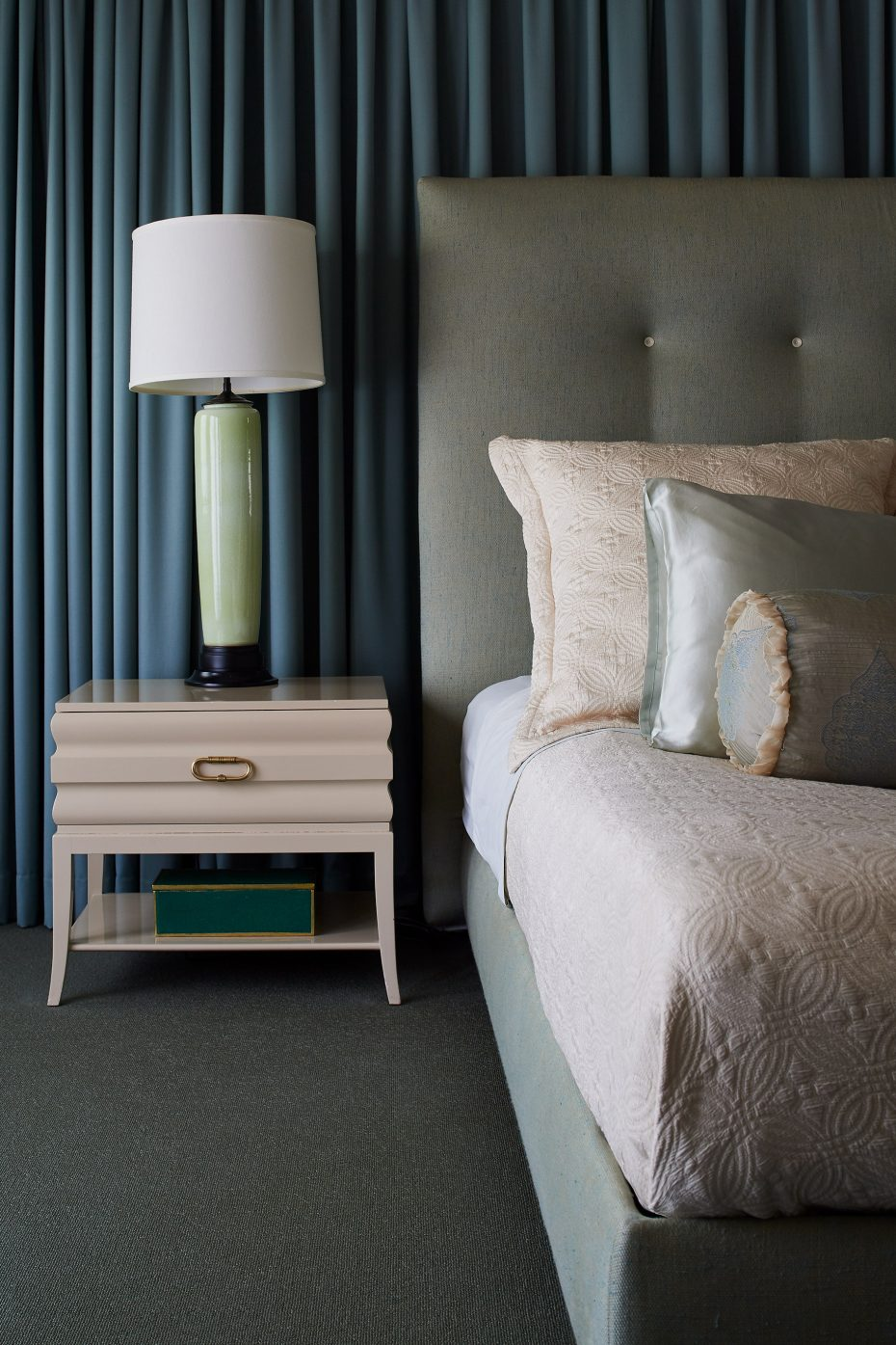 primary bedroom with upholstered tall headboard, Vintage Springer nightstands, vintage green lamps, full wall of drapery