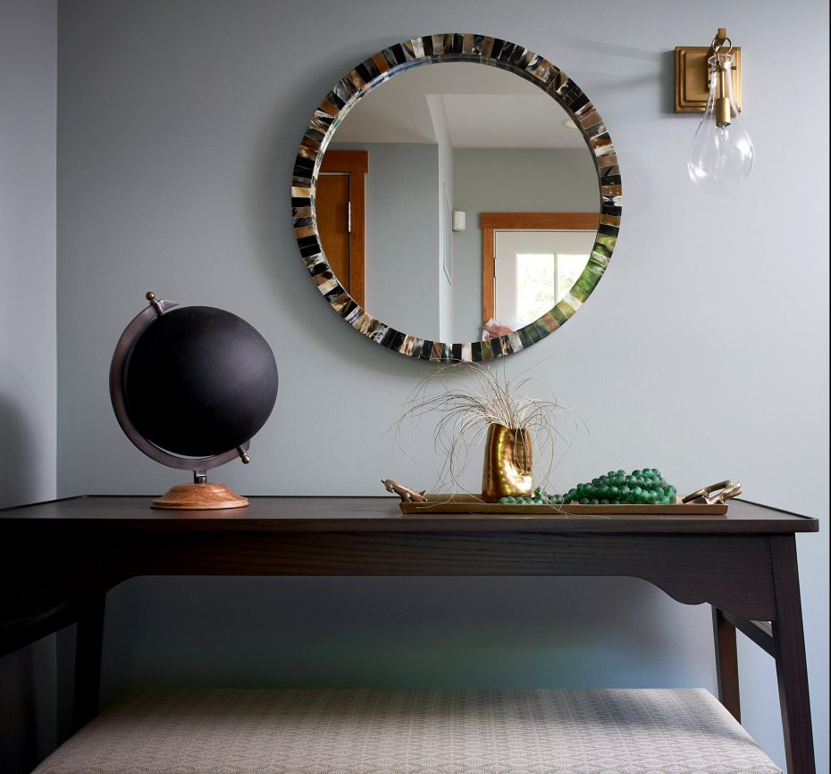 entry table in dark wood with black chalk globe and round shell mirror with brass sconce