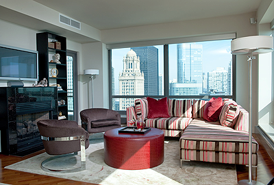 striped sectional with burgundy leather ottoman and Milo Baughman chairs
