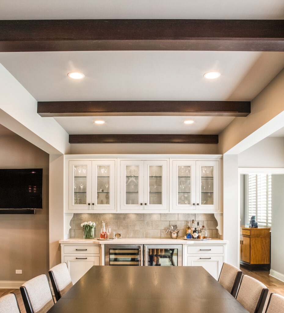 transitional style dining room with bar, white cabinets and beamed ceiling