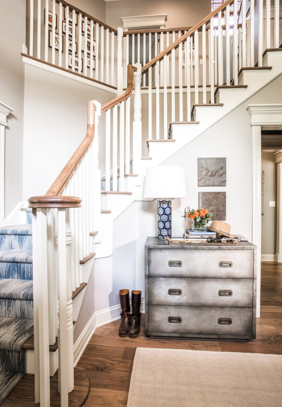 entryway with blue flame carpet runner on the stairs, metal chest of drawers and blue/white lamp