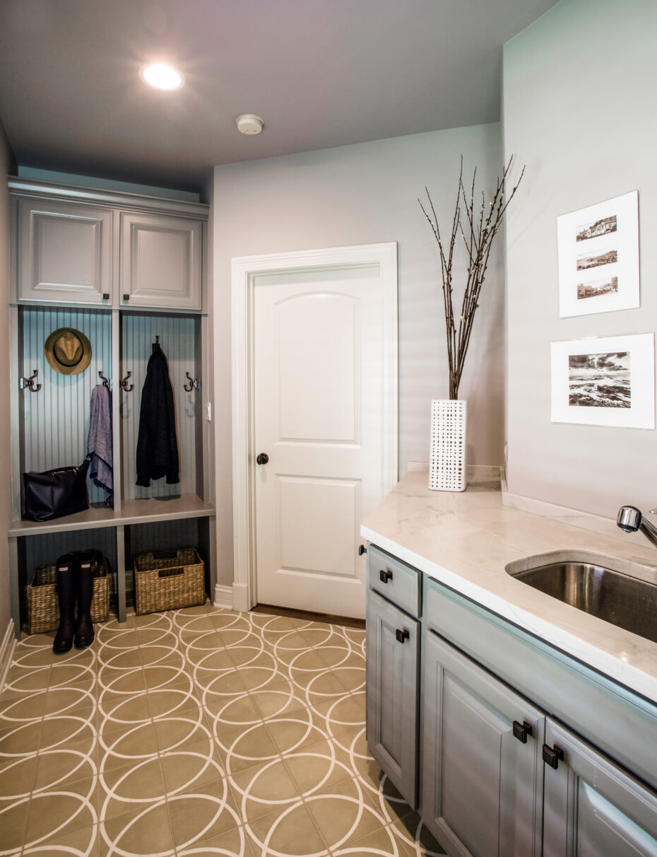 mudroom with built-in cabinets, grey cabinets, porcelain floor with circle pattern