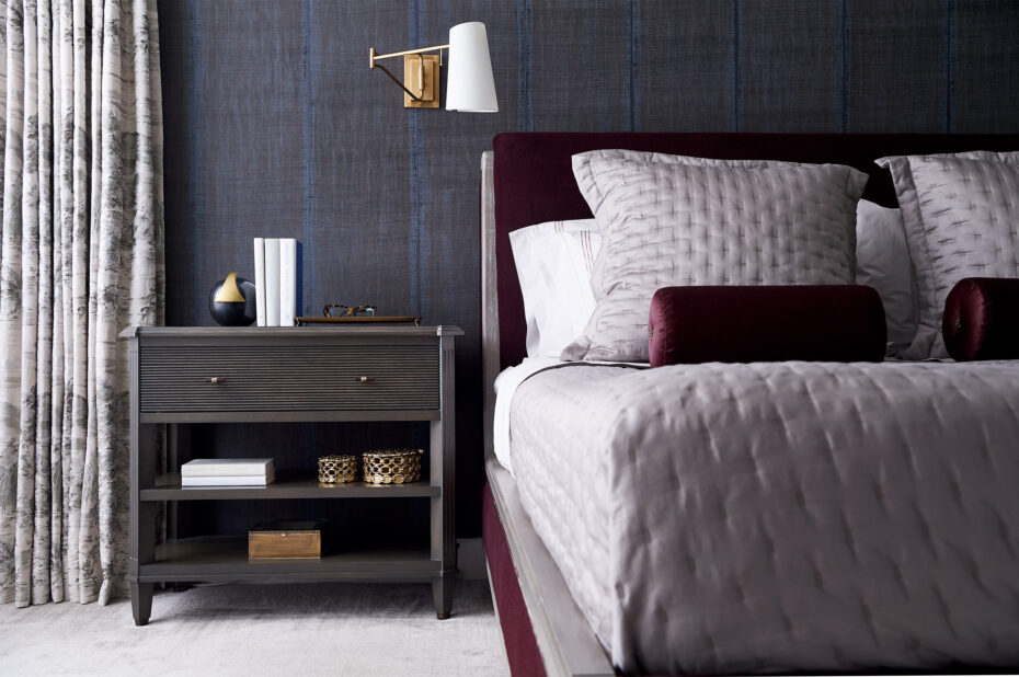 Primary bedroom with dark purple/black linen wall paper from Elitis with brass circa lighting sconces by Aerin with custom dark wood nightstands, Great Plains fabric drapery, custom bed