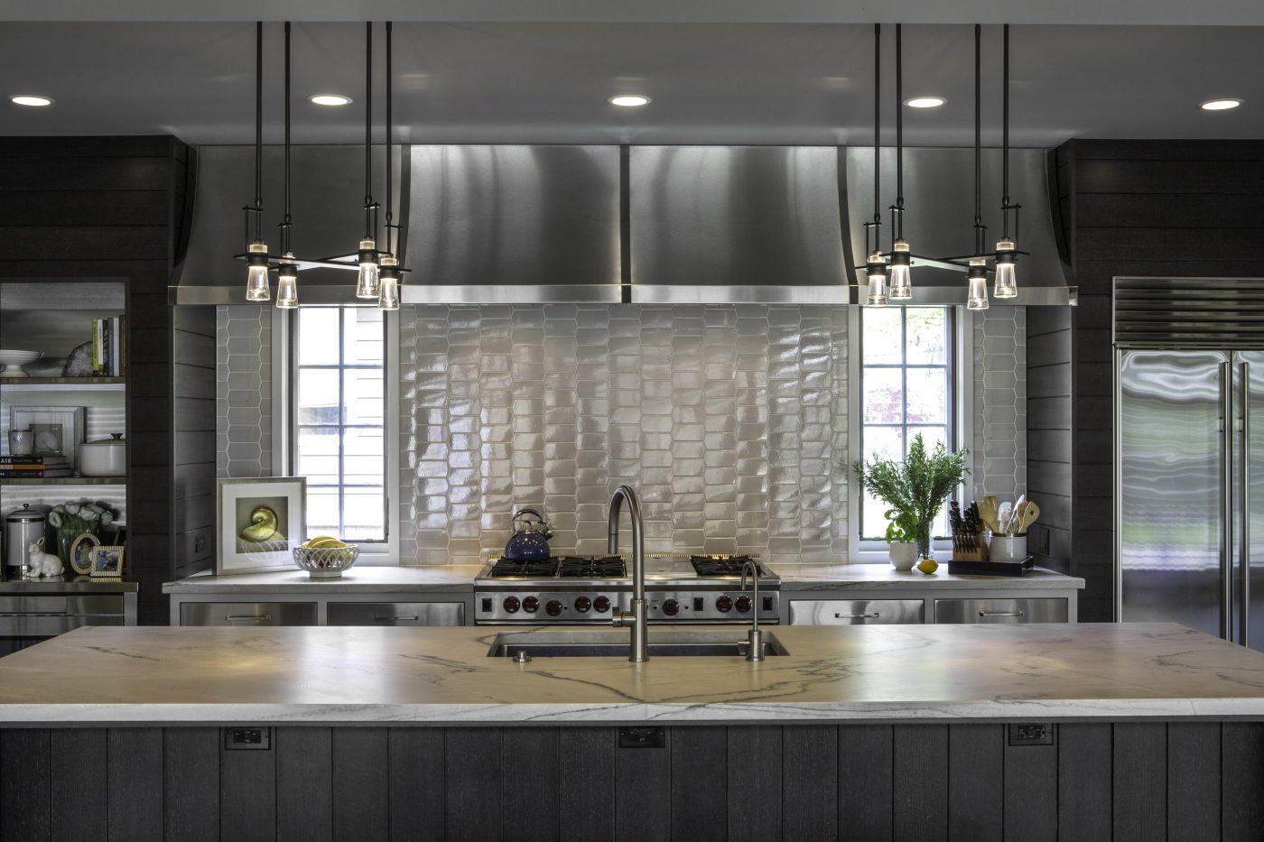 Modern kitchen design with dark walnut wood and painted cabinets. Large stainless steel vent hood over a Wolf range. Subzero refrigerator. Ann Sacks Tile. Hubbarton Forge pendant lights. White kitchen. Kitchen Renovation. Modern interior.