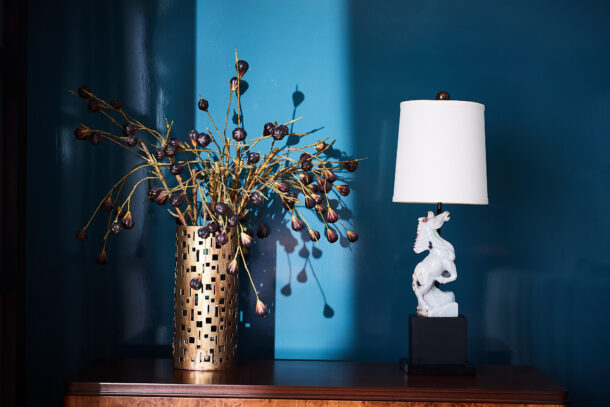 Blue lacquered walls with vintage carved stone lamp of a horse and perforated brass vase with purple flowers