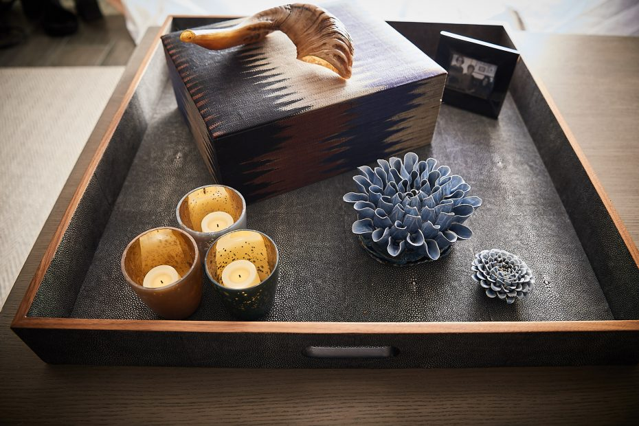 charcoal textured tray with candles, multi-colored box and blue ceramic flower