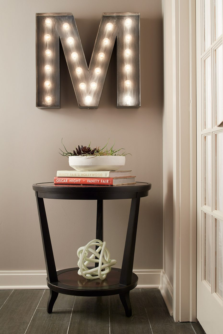 Large letter M in lights above a Hickory Chair wood table