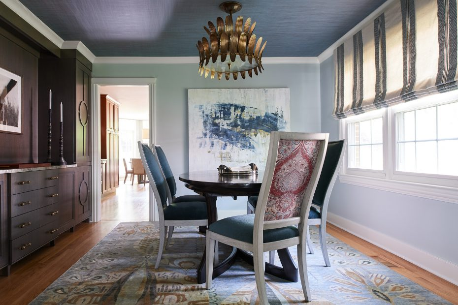 dining room with built in shelving, gold lamp from arteriors, large artwork, striped shade