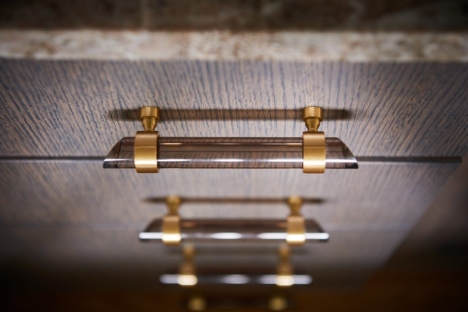 detail of brass and smoked lucite drawer pulls
