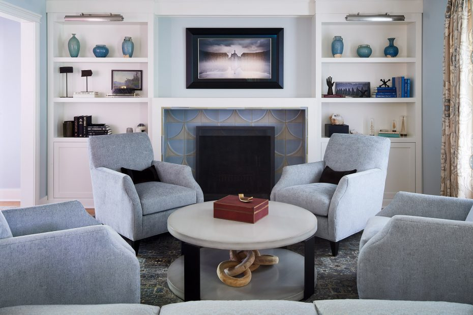 living room with blue chairs, fireplace with white bookshelves and ann sacks tile around the fireplace