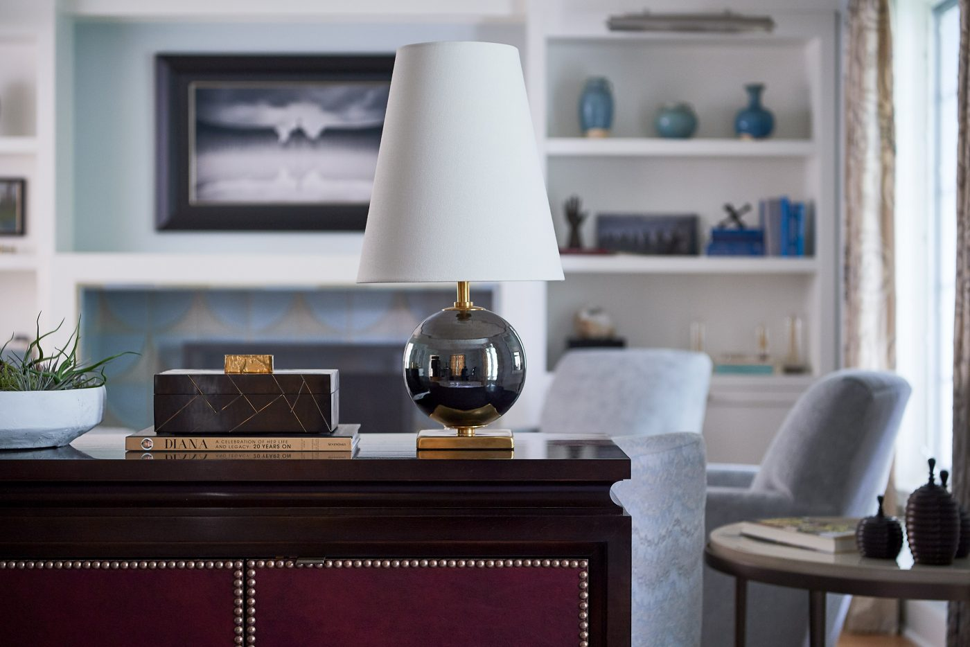 living room with a burgundy leather credenza and Circa lighting lamp in the foreground