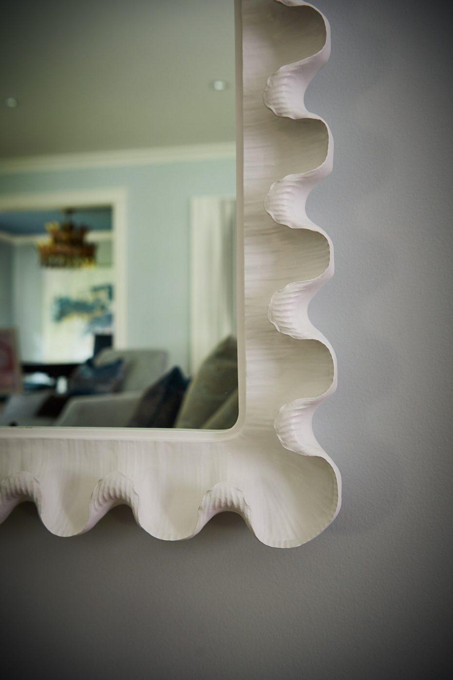 Corner of a white scalloped mirror