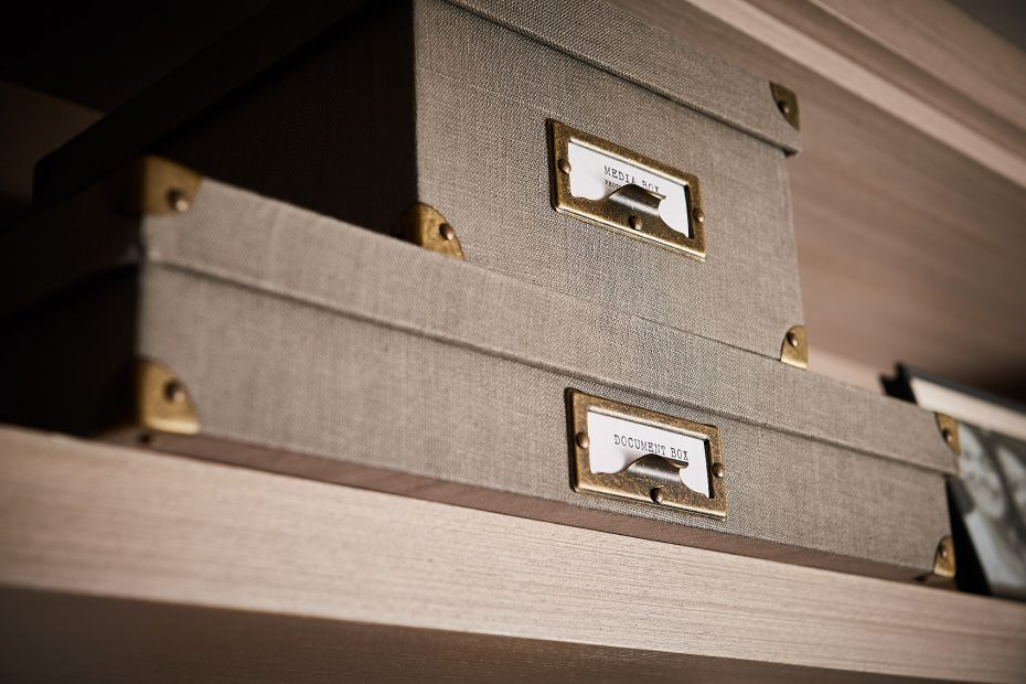 stacked beige linen boxes with metal tab labels