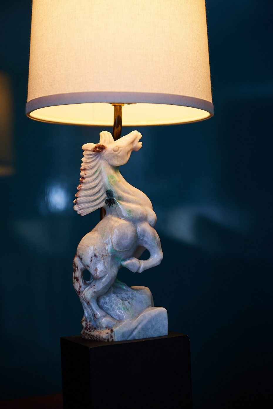 antique lamp with a white carved stone base of a horse
