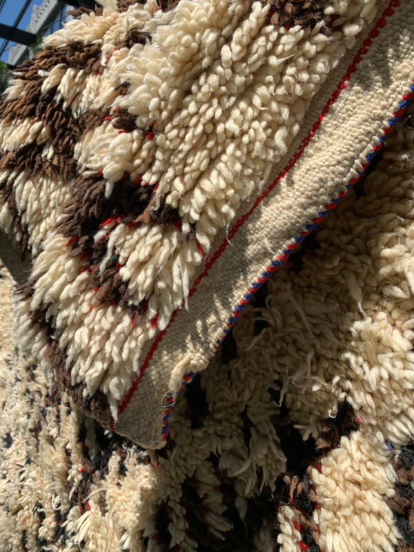 "close up of red and blue edge detail. 10-6"" x 6 Saw Moroccan rug, cream and brown with flecks of red and green. SKU 142-12 $1900"