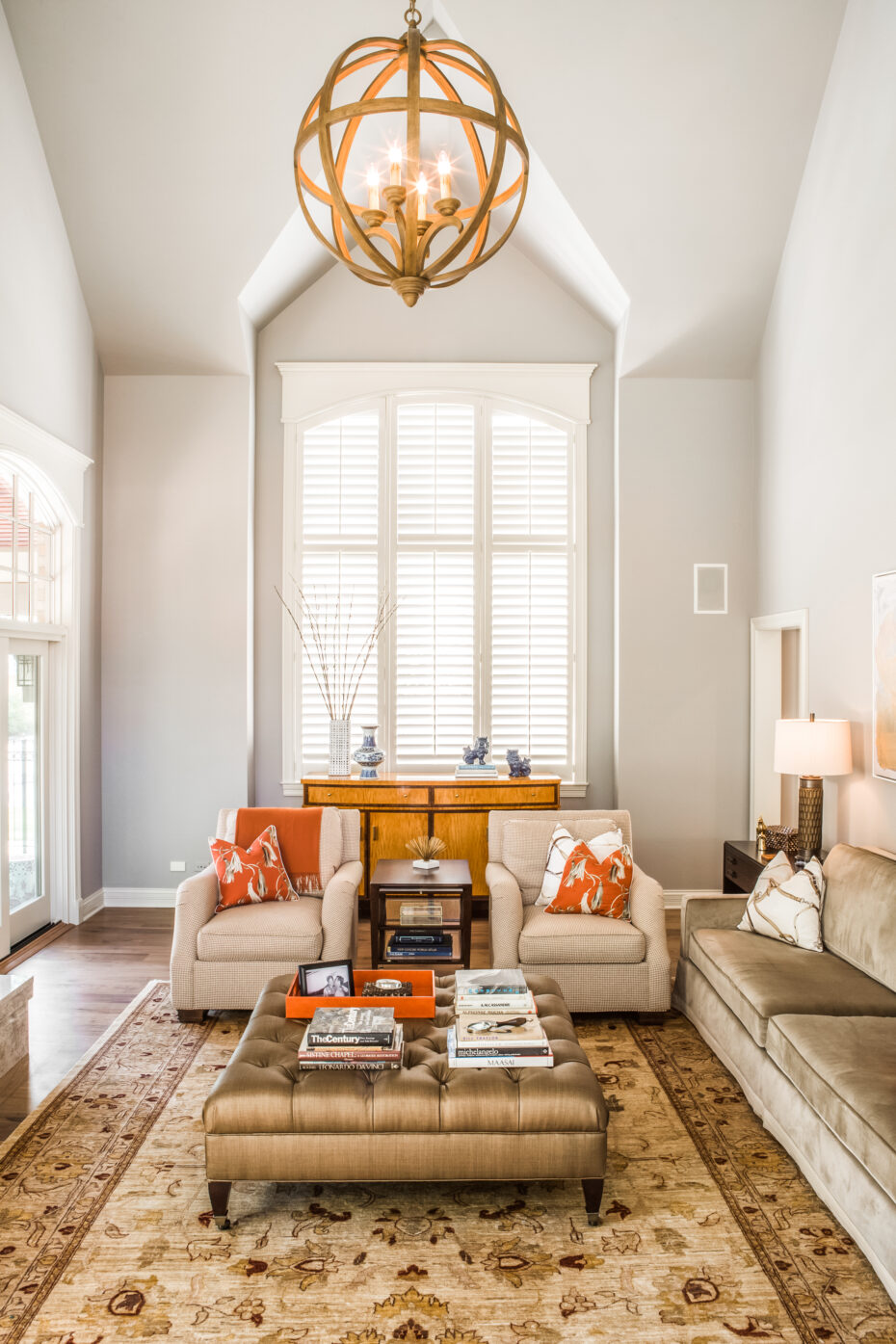 living room with volume ceilings, curry and co light fixture, neutral color with orange accents