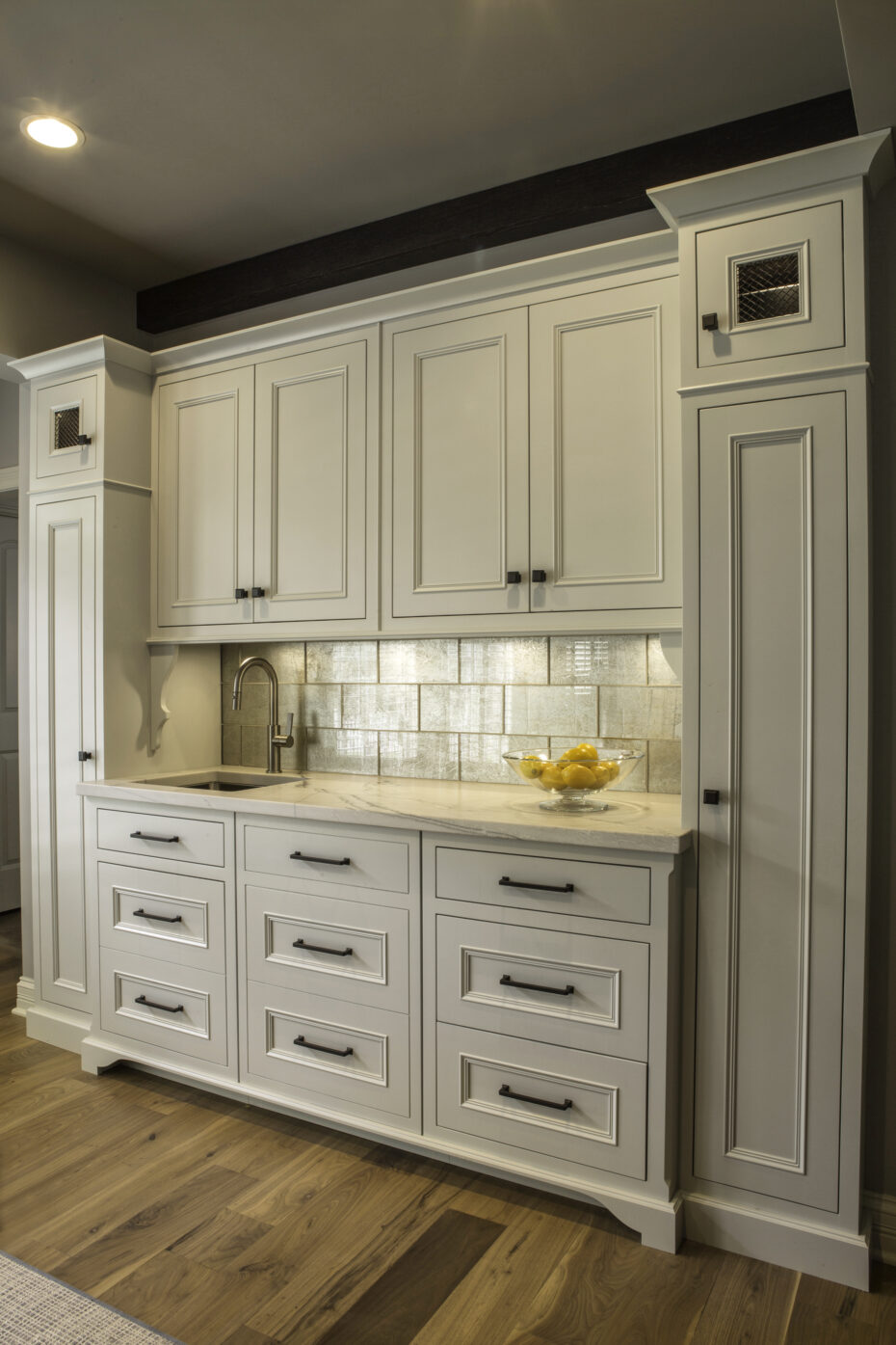 Butler's pantry with white cabinets and mirrored Ann Sacks glass tile backsplash