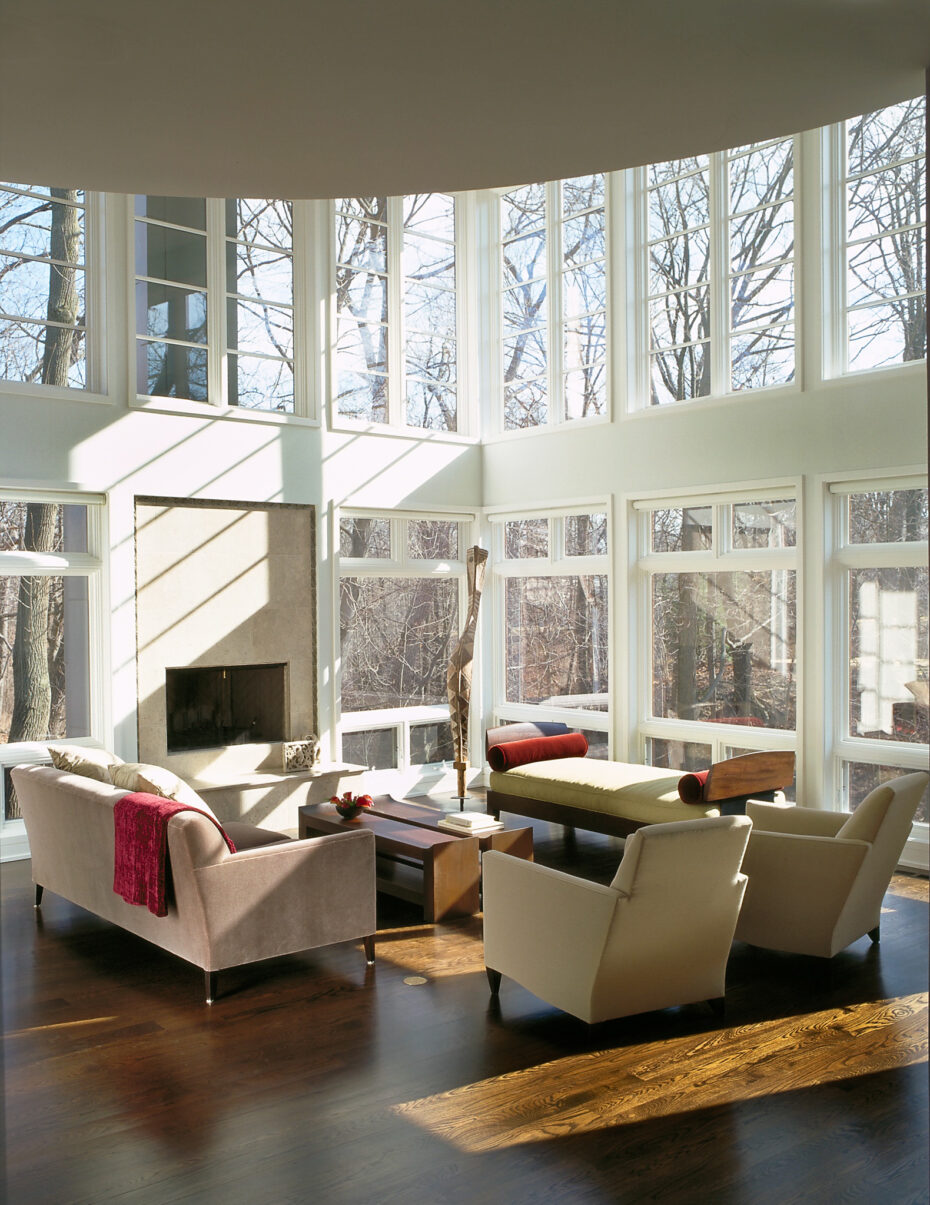 floor to ceiling windows in large modern living room with fireplace