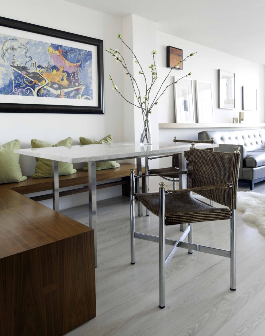 Modern dining room with a built-in walnut seat bench, stone top table, leather captains chairs with large art work