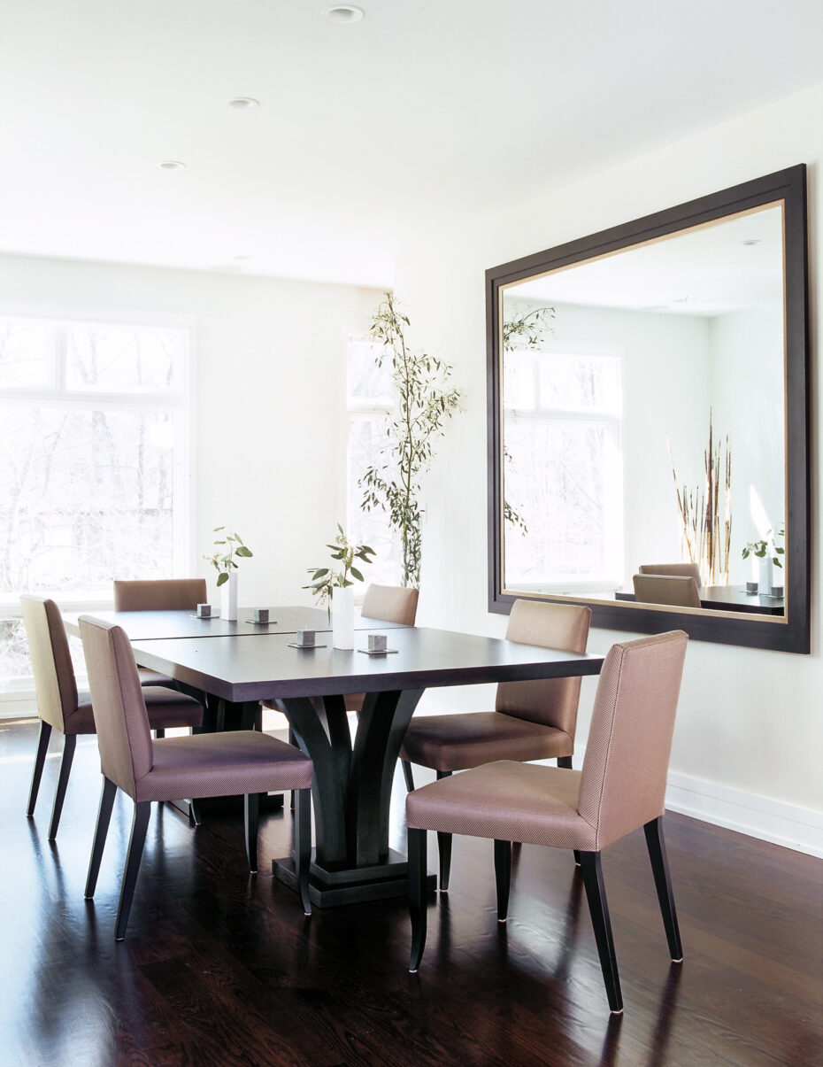 dining room with 2 square dining tables, plum colored chairs and a large mirror