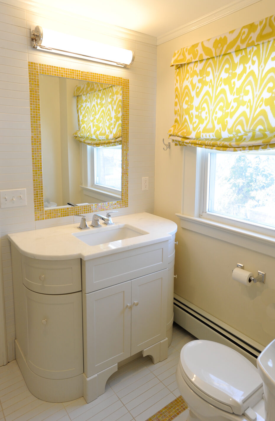 bathroom with white curved cabinet and yellow siccis glass tile